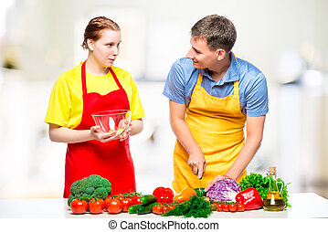 young couple preparing healthy vegetable salad in the kitchen