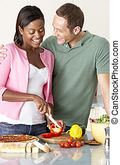 Young Couple Preparing Meal In Kitchen