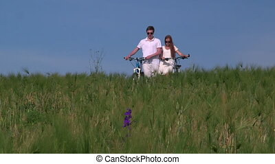 Young couple pushing bikes through the field talking...