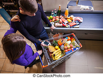 Young couple putting goods on counter in supermarket