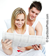 Young couple reading newspaper in bed