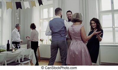 Young couple receiving presents from family on a indoor birthday party.