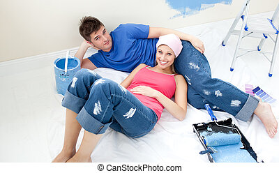 Young couple relaxing after painting a room