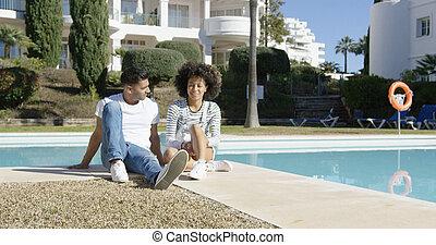 Young couple relaxing alongside an urban pool - Young couple...