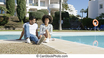 Young couple relaxing alongside an urban pool - Young couple...