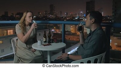 Young couple relaxing and having drinks in rooftop cafe of...
