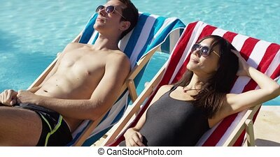 Young couple relaxing at a resort swimming pool