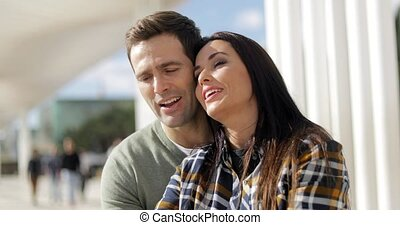 Attractive affectionate young couple relaxing at an urban waterfront sitting curled up together outdoors on a bench enjoying the sunshine