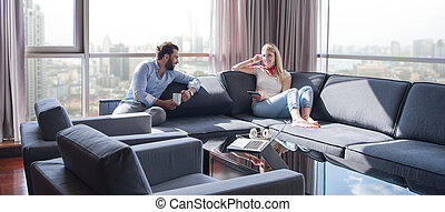 couple relaxing at home using tablet computer - Young couple...