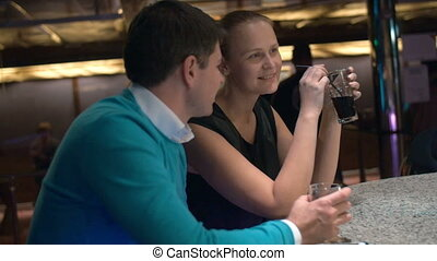 Young couple relaxing in bar and having drinks