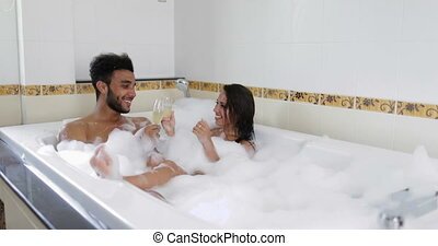 Young Couple Relaxing In Bath Together Drink Champagne, Man...