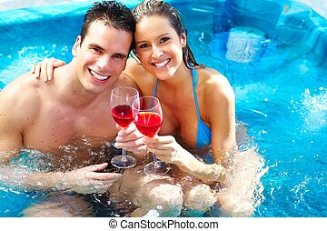 Young couple relaxing in jacuzzi. - Young couple relaxing in...
