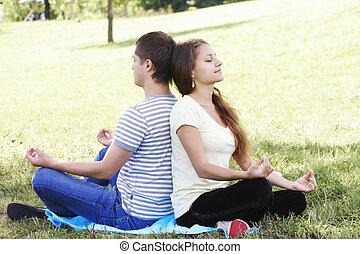 Young couple relaxing in yoga pose