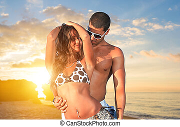 young couple relaxing on the beach at sunset