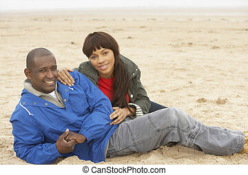 Young Couple Relaxing On Winter Beach Holiday