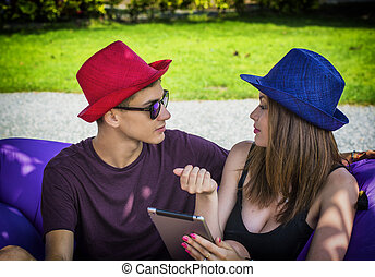 Young couple relaxing outside looking at cellphone