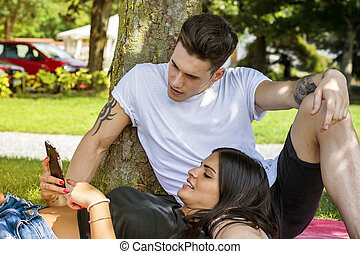 Young couple relaxing outside looking at tablet