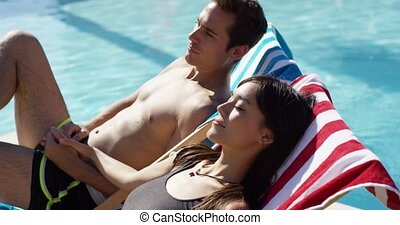 Young couple relaxing poolside in deck chairs