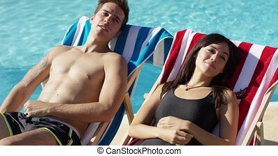 Young couple relaxing poolside in deck chairs smiling...