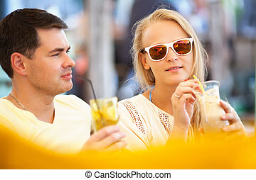 Young couple relaxing with refreshing drinks