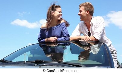 Young couple rest on front window of cabriolet and talk