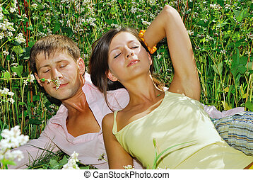 Young couple resting on field of flowers