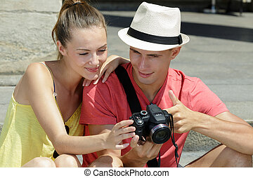 young couple reviewing photographs on camera display