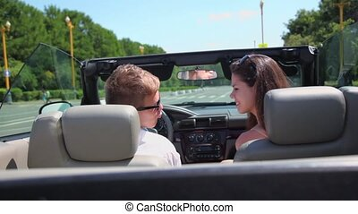 Young couple ride in cabriolet and turn around on street