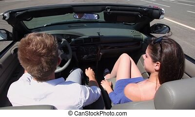 Young couple ride in cabriolet by road, behind view from above