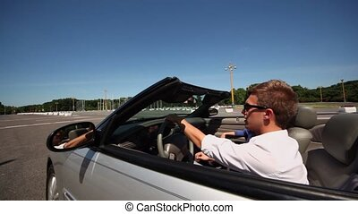 Young couple ride in cabriolet by road at sunny summer day