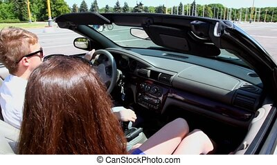 Young couple ride in cabriolet by street, closeup view