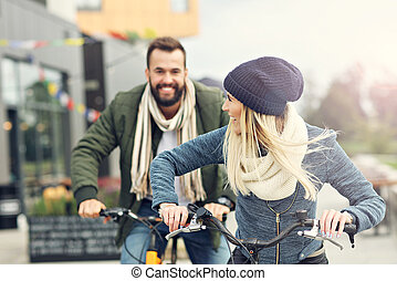 Young couple riding bikes and having fun in the city