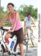 Young couple riding bikes in the countryside