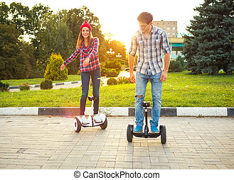 Young couple riding hoverboard - electrical scooter, personal eco transport, gyro scooter, smart balance wheel