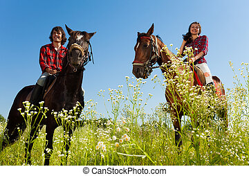 Young couple riding purebred horses at countryside