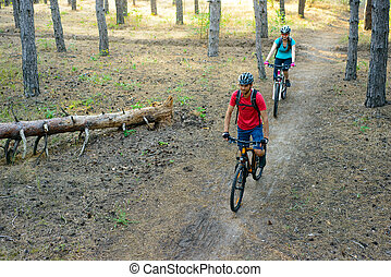 Young Couple Riding the Mountain Bikes in the Pine Forest. Adventure and Family Travel Concept.