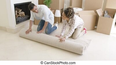 Young couple rolling up a rug as they move house
