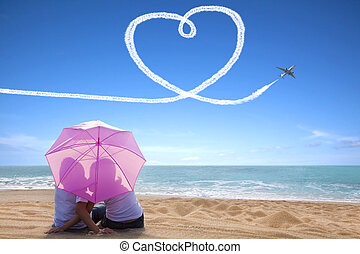 young couple romantic kissing at the beach with the umbrella