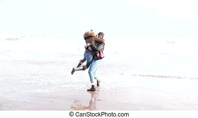 Young Couple Run In The Waves On Winter Beach - A young...