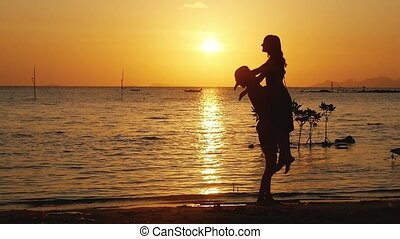 Young couple run to each other, man hug and spin around his woman on beautiful sunset. Having fun together at vacation. Slow motion.
