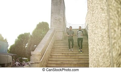 Young couple runners running down the stairs in the city. -...