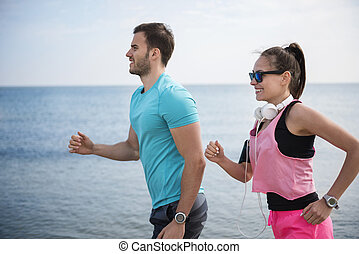 Young couple running by the ocean