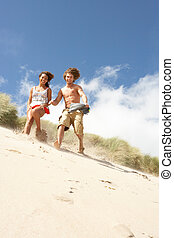 Young Couple Running Down Sand Dune On Beach