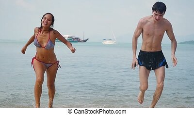 Young couple running from tropical sea on the beach in slow motion.