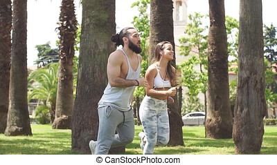 Young couple running in park in summer morning