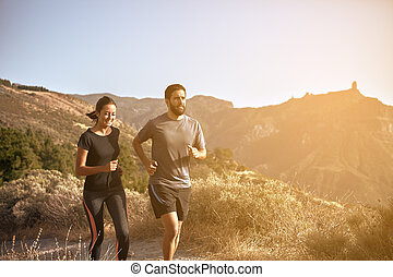 Young couple running in the mountains