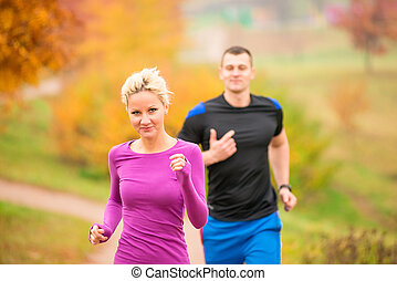 young couple running in the park in autumn morning