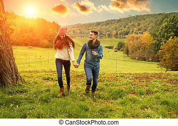 Young couple running on the beautiful scenery