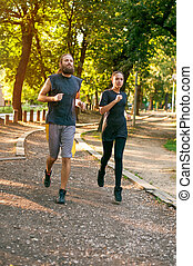 Young couple running on the jogging track through the forest