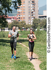 Young Couple Running Outdoors On A Lovely Day
